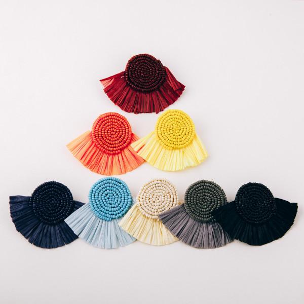 "Seed beaded felt disc earrings featuring raffia tassel details. Approximately 2"" in length."