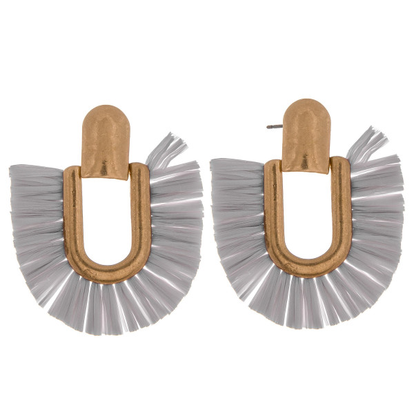 "Metal drop earrings featuring raffia tassel details and a stud post. Approximately 2"" in length."