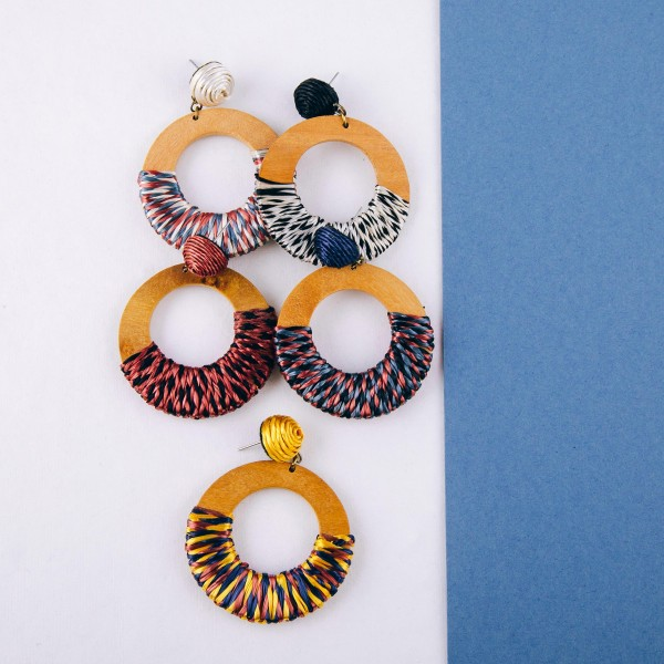 """Raffia wrapped open circle wood earrings. Approximately 2.5"""" in length and 1.75"""" in diameter."""