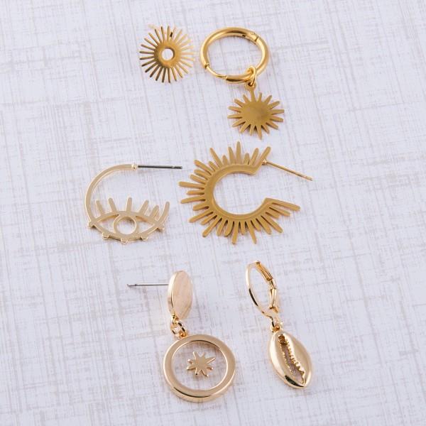 "Gold puka shell huggie hoop earrings.  - Approximately 1"" in length"