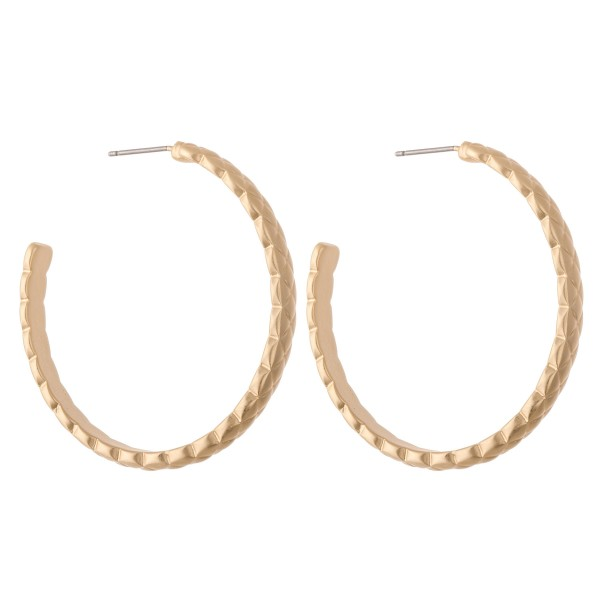 "Metal hoop earrings featuring textured details.  - Approximately 1.5"" in diameter"