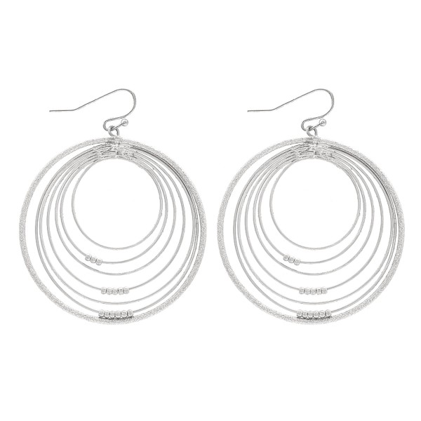 "Circular metal earrings featuring a modern design and small circular details.  - Approximately 2"" in diameter"