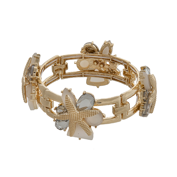 Gold tone stretch bracelet displaying white and clear cabochons with layered starfish.