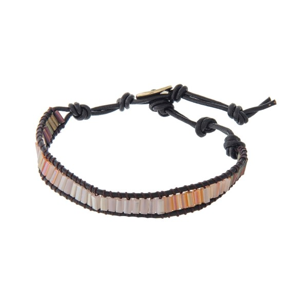 Brown cord bracelet with peach beads and a button closure.