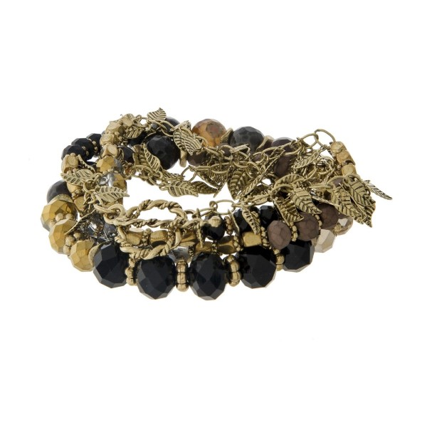 "Gold tone toggle bracelet with gold leaf charms, brown and black beads. Can also be worn as a necklace. Approximately 24"" in length."