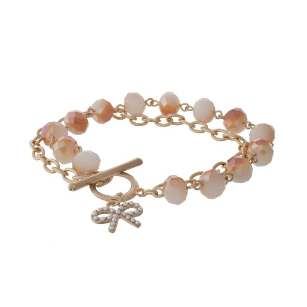 Gold tone toggle bracelet with champagne faceted beads and a bow charm.