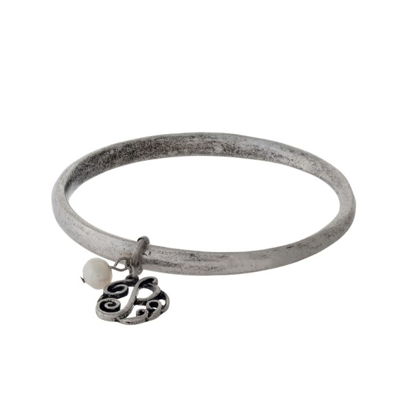 Burnished silver tone bangle bracelet with a script 'P' initial and freshwater pearl charm.
