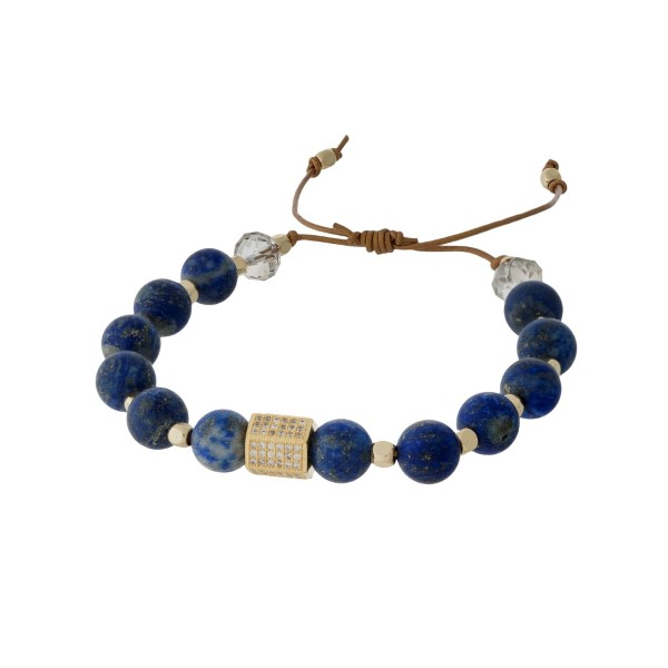 Adjustable cord bracelet with lapis natural stone beads, gold tone square beads, and clear rhinestones. Handmade in the USA.