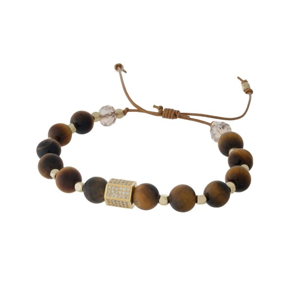 Adjustable cord bracelet with tiger's eye natural stone beads, gold tone square beads, and clear rhinestones. Handmade in the USA.