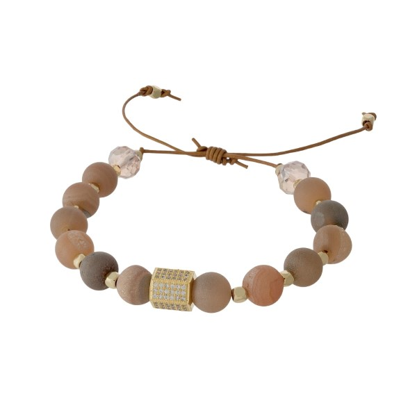 Adjustable cord bracelet with peach druzy natural stone beads, gold tone square beads, and clear rhinestones. Handmade in the USA.
