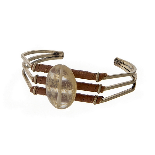 Burnished gold tone cuff bracelet with tan leather and a beige oval stone.