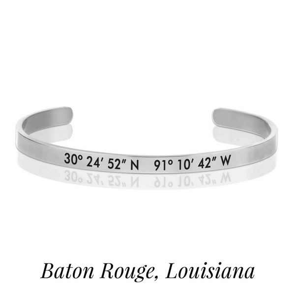 Silver tone cuff bracelet stamped with the coordinates of Baton Rouge, Louisiana.