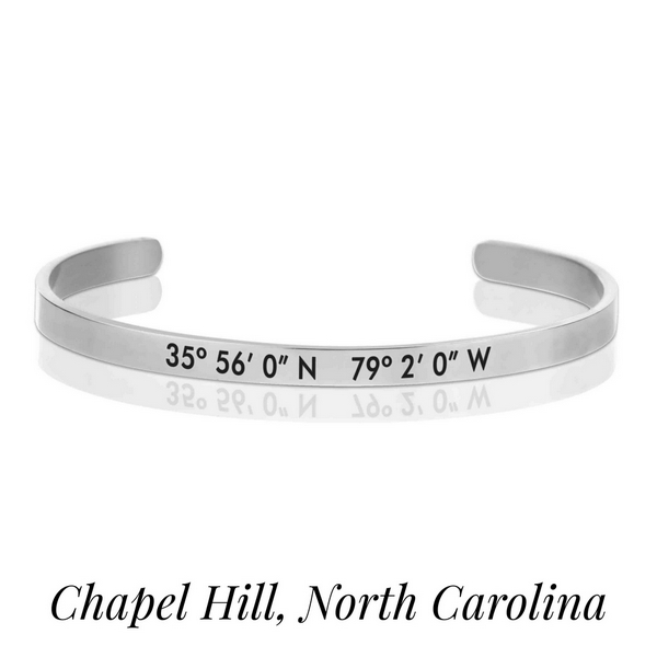 Silver tone cuff bracelet stamped with the coordinates of Chapel Hill, North Carolina.