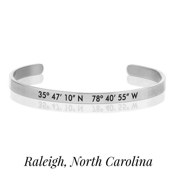 Silver tone cuff bracelet stamped with the coordinates of Raleigh, North Carolina.