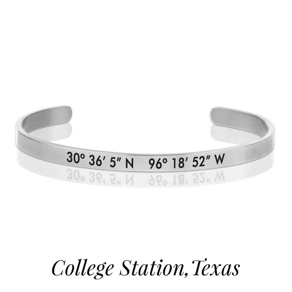 Silver tone cuff bracelet stamped with the coordinates of College Station, Texas.