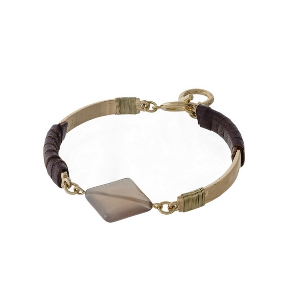 Gold tone toggle bracelet with brown wrapped leather and a gray natural stone.