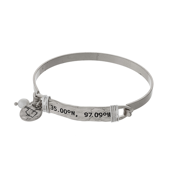 Silver tone bangle bracelet stamped with the coordinates of Oklahoma, accented with a pearl bead and a Oklahoma charm.