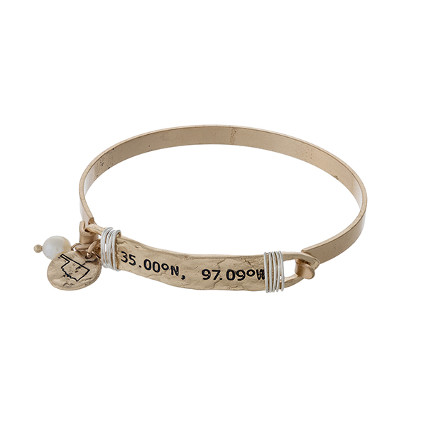 Gold tone bangle bracelet stamped with the coordinates of Oklahoma, accented with a pearl bead and an Oklahoma charm.