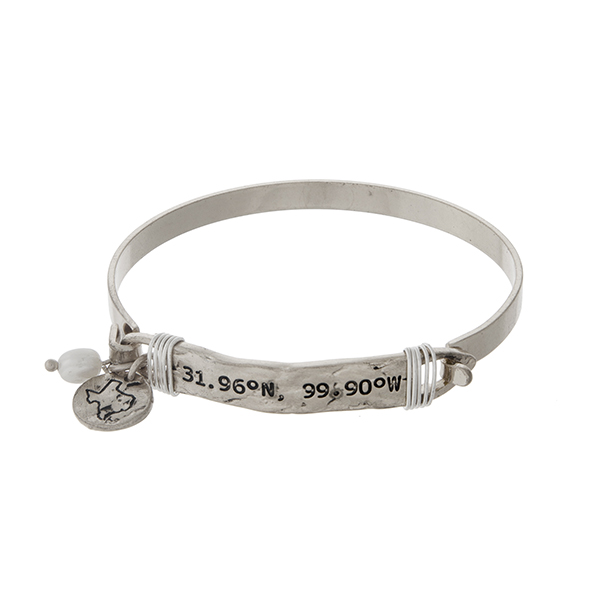 Silver tone bangle bracelet stamped with the coordinates of Texas, accented with a pearl bead and a Texas charm.