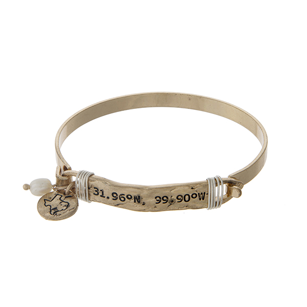 Gold tone bangle bracelet stamped with the coordinates of Texas, accented with a pearl bead and a Texas charm.