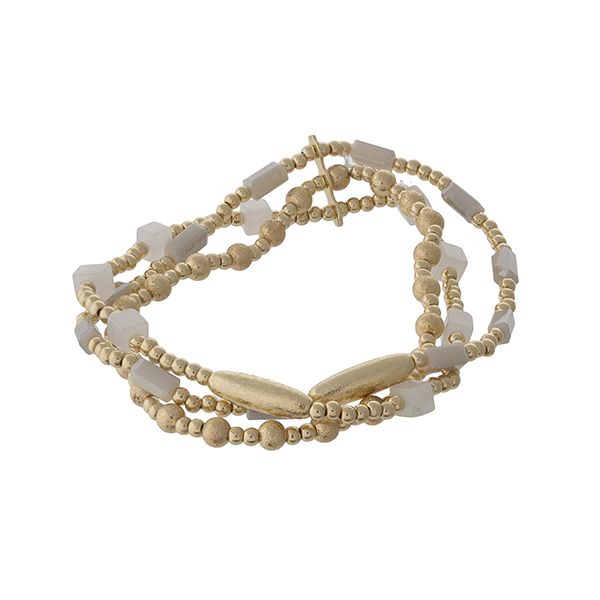 Gold tone and white beaded, stretch bracelet set.
