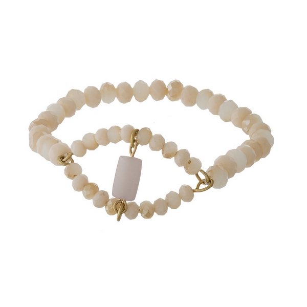 Ivory and champagne beaded stretch bracelet featuring a small rose quartz stone.