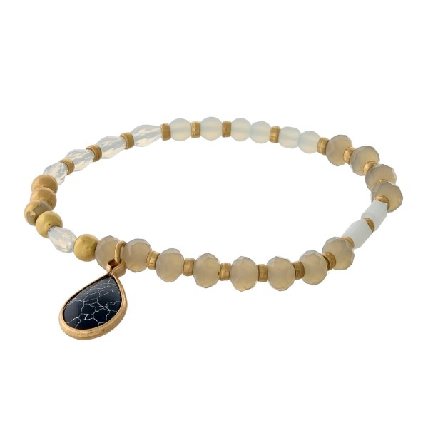 Gray and gold tone beaded bracelet with a black charm.