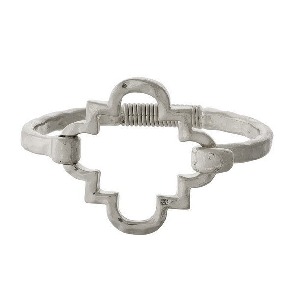 Silver tone bangle bracelet with a spring hinge and an open quatrefoil shape.