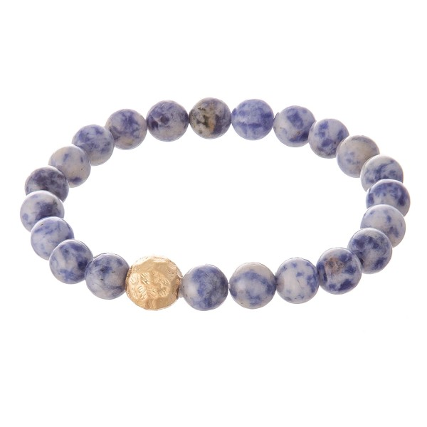 """Blue beaded stretch bracelet with a gold accent. Approximately 2.5"""" in diameter unstretched. Fits up to a 5"""" wrist."""