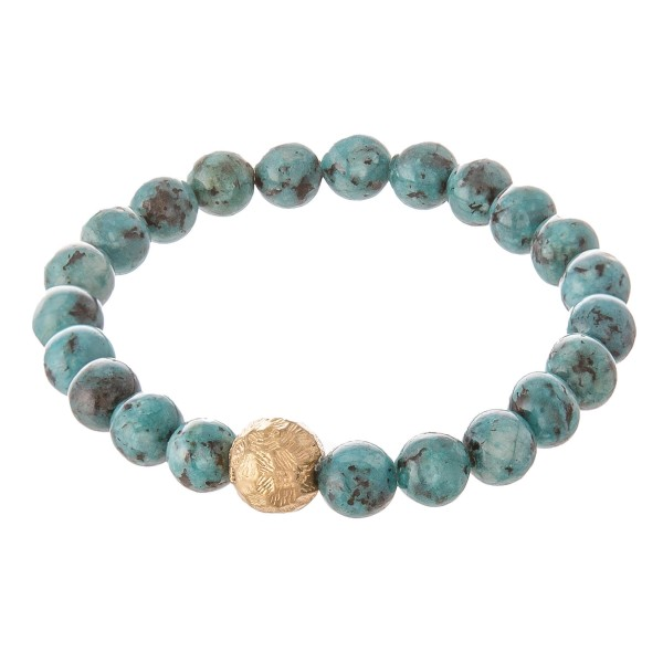 """Green beaded stretch bracelet with a gold accent. Approximately 2.5"""" in diameter unstretched. Fits up to a 5"""" wrist."""