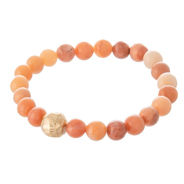 """Peach beaded stretch bracelet with a gold accent. Approximately 3"""" in diameter unstretched. Fits up to a 6"""" wrist."""