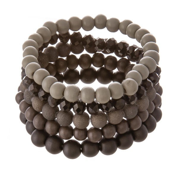 """Bracelet set featuring three wood beaded bracelets with one faceted acrylic beaded stand and one ceramic glitter beaded stand. Approximately 2.5"""" in diameter unstretched. Fits up to a 5"""" wrist."""