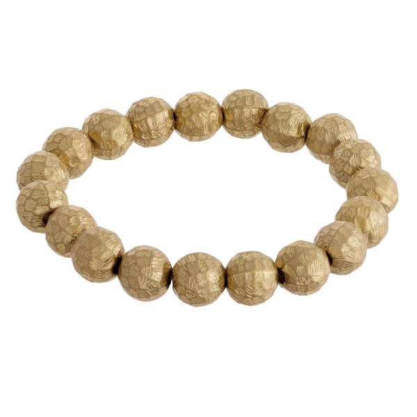 "Gold stretch bracelet featuring metal hammered beaded details. Approximately 2.75"" in diameter unstretched. Fits up to a 6"" wrist."