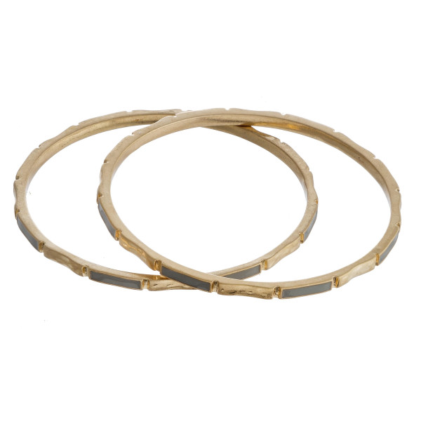 """Metal bangle bracelet featuring grey and gold accents. Approximately 2.75"""" in diameter. Fits up to a 5.5"""" wrist."""