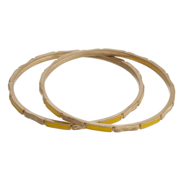 """Metal bangle bracelet featuring yellow and gold accents. Approximately 2.75"""" in diameter. Fits up to a 5.5"""" wrist."""