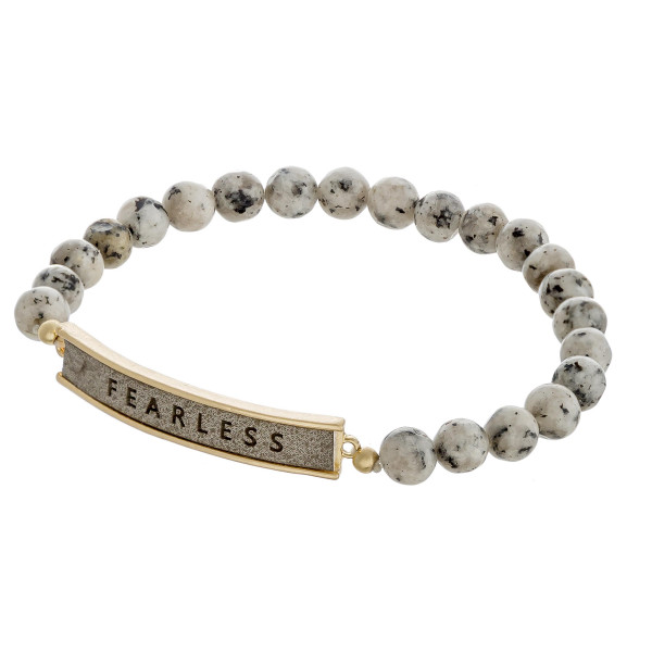"Natural stone beaded stretch bracelet featuring a faux leather focal with ""Fearless"" engraved details. Approximately 3"" in diameter unstretched. Fits up to a 6"" wrist."