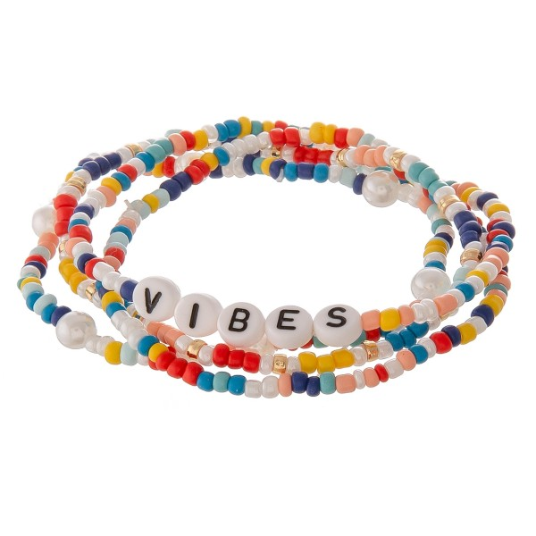 "Multicolor seed beaded ""Vibes"" letter stretch bracelet set with pearl details.  - 4pcs/pack - Approximately 3"" in diameter unstretched - Fits up to a 7"" wrist"