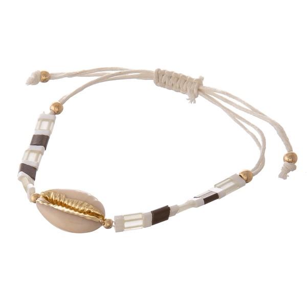 "Miyuki Tila beaded puka shell bolo cord bracelet.  - Ajustable bolo closure - Approximately 3"" in diameter - Fits up to an 8"" wrist"