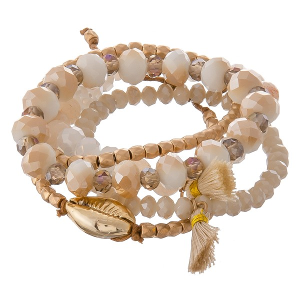 """Semi precious puka shell bolo cord stretch bracelet set with tassels.  - 5pcs/set - Adjustable bolo strand - Approximately 3"""" in diameter unstretched - Fits up to an 8"""" wrist"""