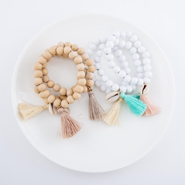 "Wood Beaded Puka Shell Tassel Stretch Bracelet Set.  - 3pcs/set - Approximately 3"" in diameter - Fits up to a 7"" wrist"