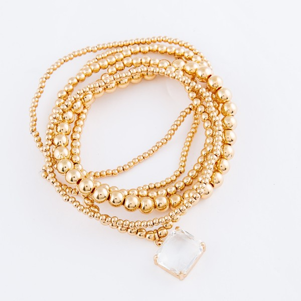 """Gold Ball Beaded Stretch Bracelet Set with Crystal Clear Charm.  - 6pcs/set - Bead Sizes 1mm, 2mm and 4mm  - Approximately 3"""" in diameter - Fits up to a 7"""" wrist"""
