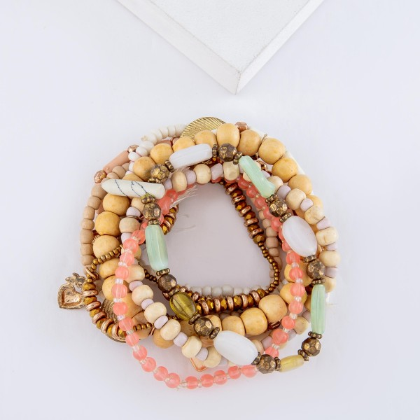 "Ivory Pink Semi Precious Wood Beaded Boho Charm Tassel Stretch Bracelet Set with Feather, Shell and Heart Details.  - 10pcs/set - Approximately 3"" in diameter - Fits up to a 7"" wrist"