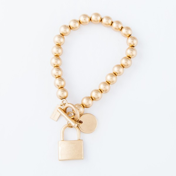 "CCB Toggle Bar Lock Charm Stretch Bracelet in Gold.  - Lock Charm .75"" - Approximately 3"" in diameter - Fits up to a 7"" wrist"