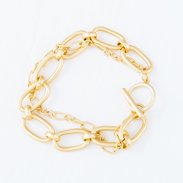 "Chain Link Layered Toggle Bar Bracelet in a Matte Gold Finish.  - Approximately 2.5"" in diameter - Fits up to a 6"" wrist - 1"" Adjustable Extender"