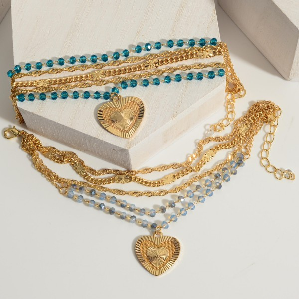 """Layered Gold Chain Bracelet Featuring Beaded Accents and a Heart Pendant.   - Lobster Clasp Closure  - Approximately 3"""" in Diameter  - Adjustable 2"""" Extender"""
