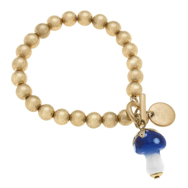 "Beaded Glass Mushroom Charm Stretch Bracelet in Worn Gold.  - Charm 1""  - Toggle Bar Clasp - Approximately 3"" in Diameter"