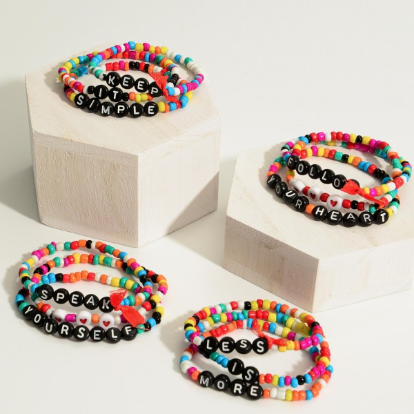 "Set of Three Multicolored Beaded Bracelets Featuring Red Ribbon Accents.   - Approximately 3"" in Diameter"