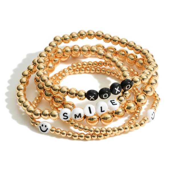 """Set of Five Gold Beaded Bracelets Featuring Letter Beads that Say """"XOXO"""" and """"Smile"""" with Smiley Face Accents.   - Approximately 3"""" in Diameter"""