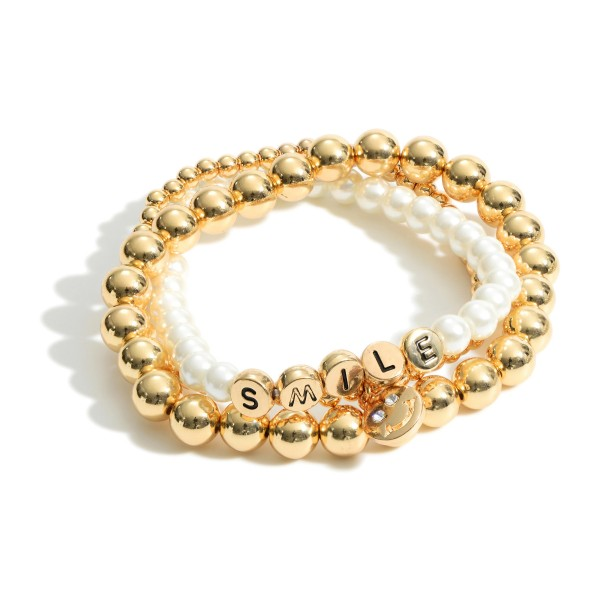 """Set of Three Beaded Stretch Bracelets Featuring Faux Pearl Accents, Smiley Face Pendant, and Metal Letter Beads that Spell """"Smile"""".   - Approximately 3"""" in Diameter"""