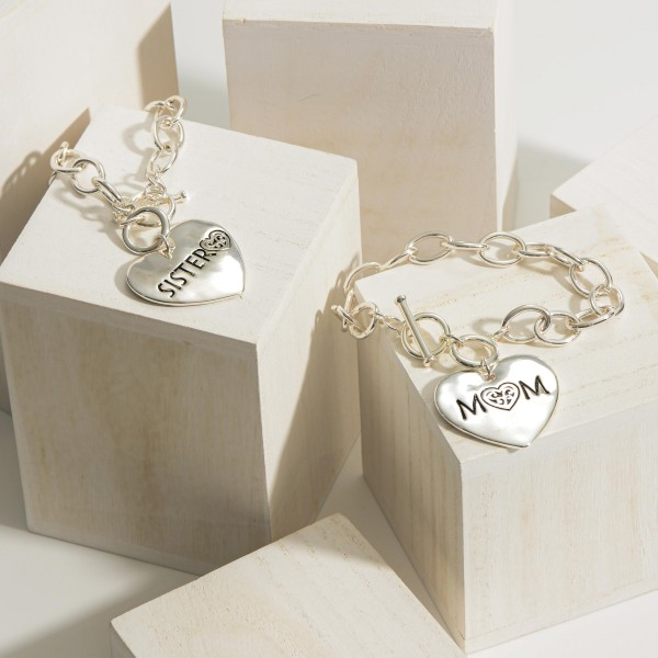 "Silver Chain Bracelet with Toggle Clasp Featuring Heart Shaped Pendant that Says ""Sister"".   - Approximately 3"" in Diameter"